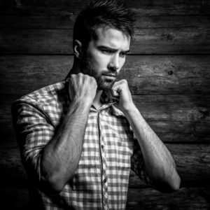 Black-white portrait of young beautiful fashionable man against wooden wall.